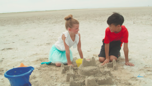 "One Voice Children's Choir music video for ""Something Just Like This"" where boy and girl are building a sandcastle"